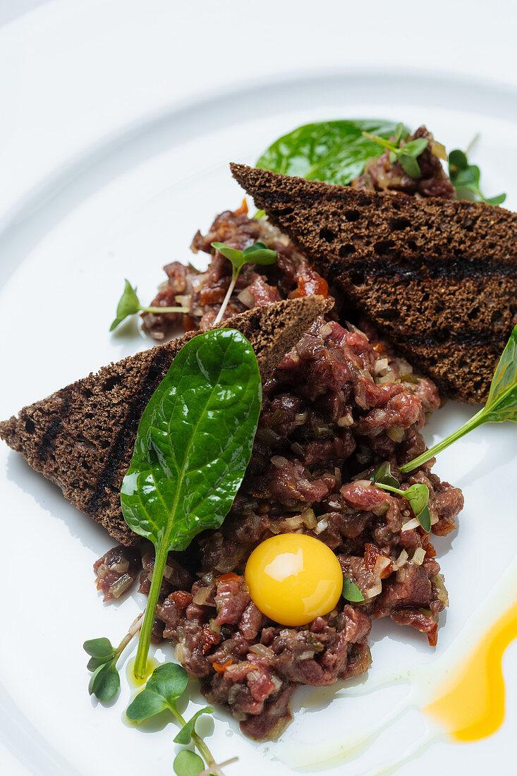 Tartar mit dunklem Toastbrot und Eigelb