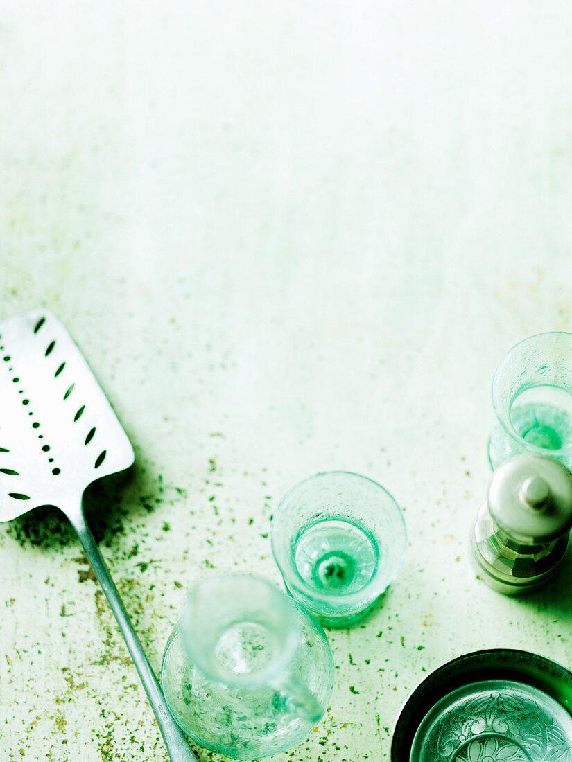 Utensils (Spatula, glasses, pepper mill) on green surface