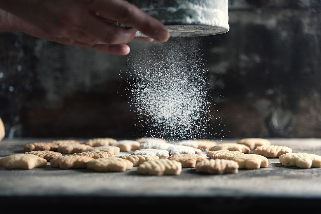 Dusting flower-shaped cookies with icing sugar