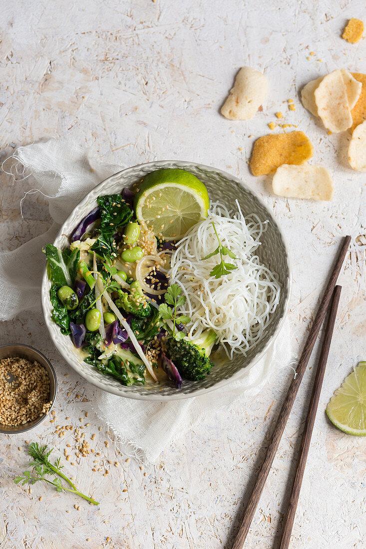 Buddha comfort bowl of vegan Thai green stir fry with rice noodles