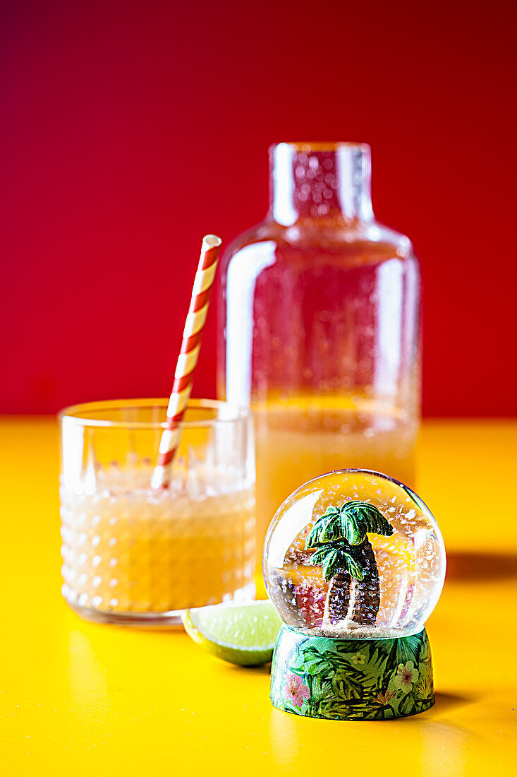 Iced tea with pineapple and coconut syrup in front of a snow globe with a mini palm tree