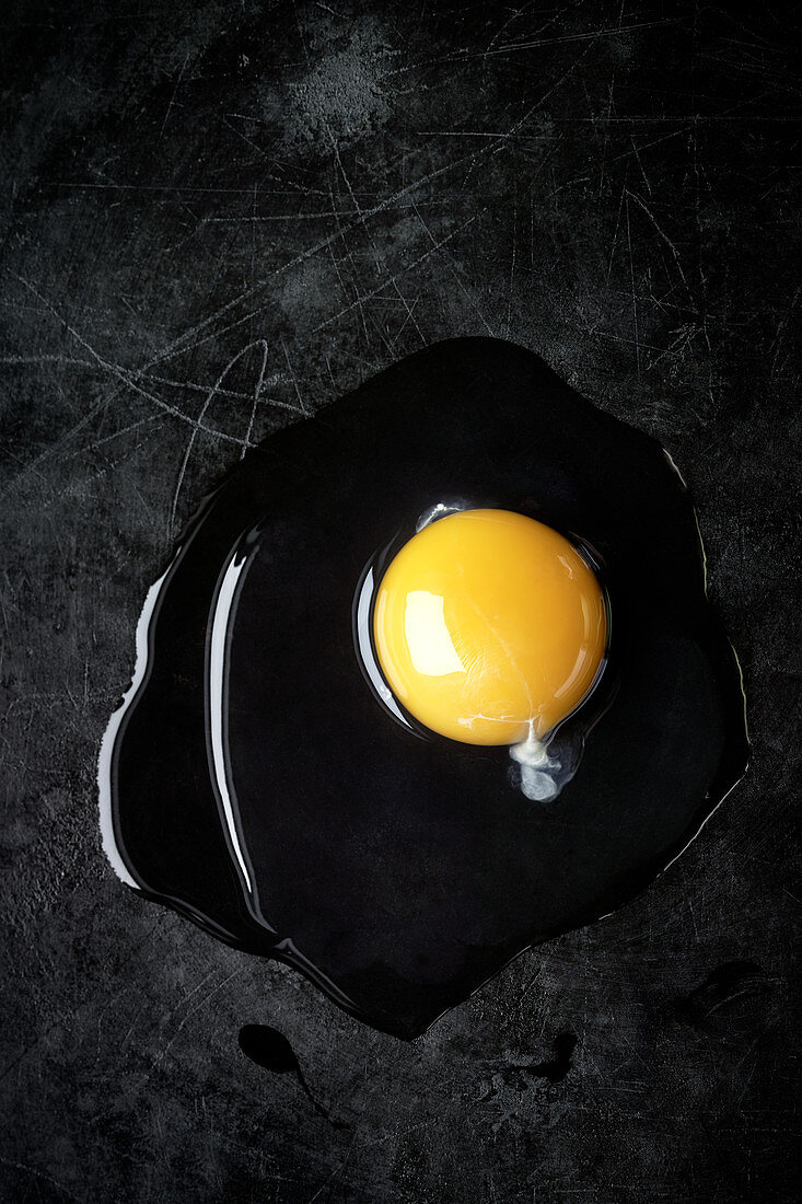 An open egg on a black metal background