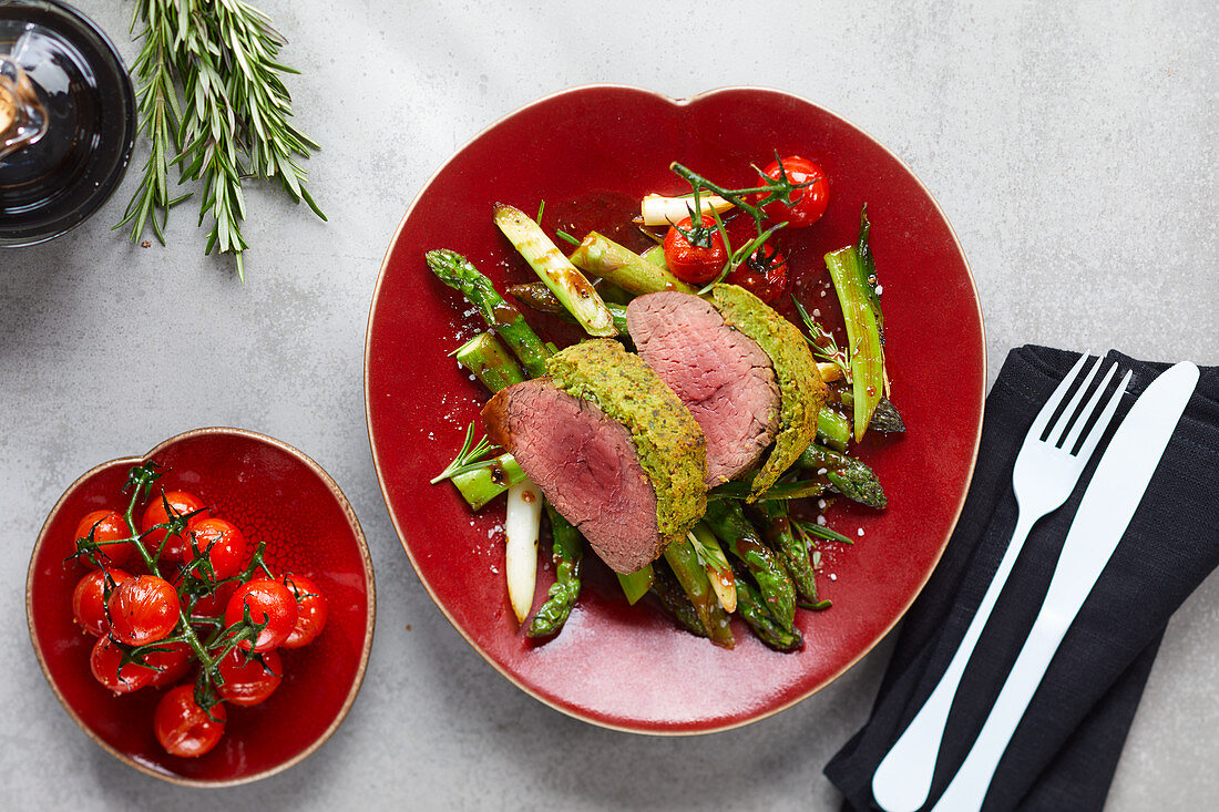Beef fillet with herb crust on green asparagus