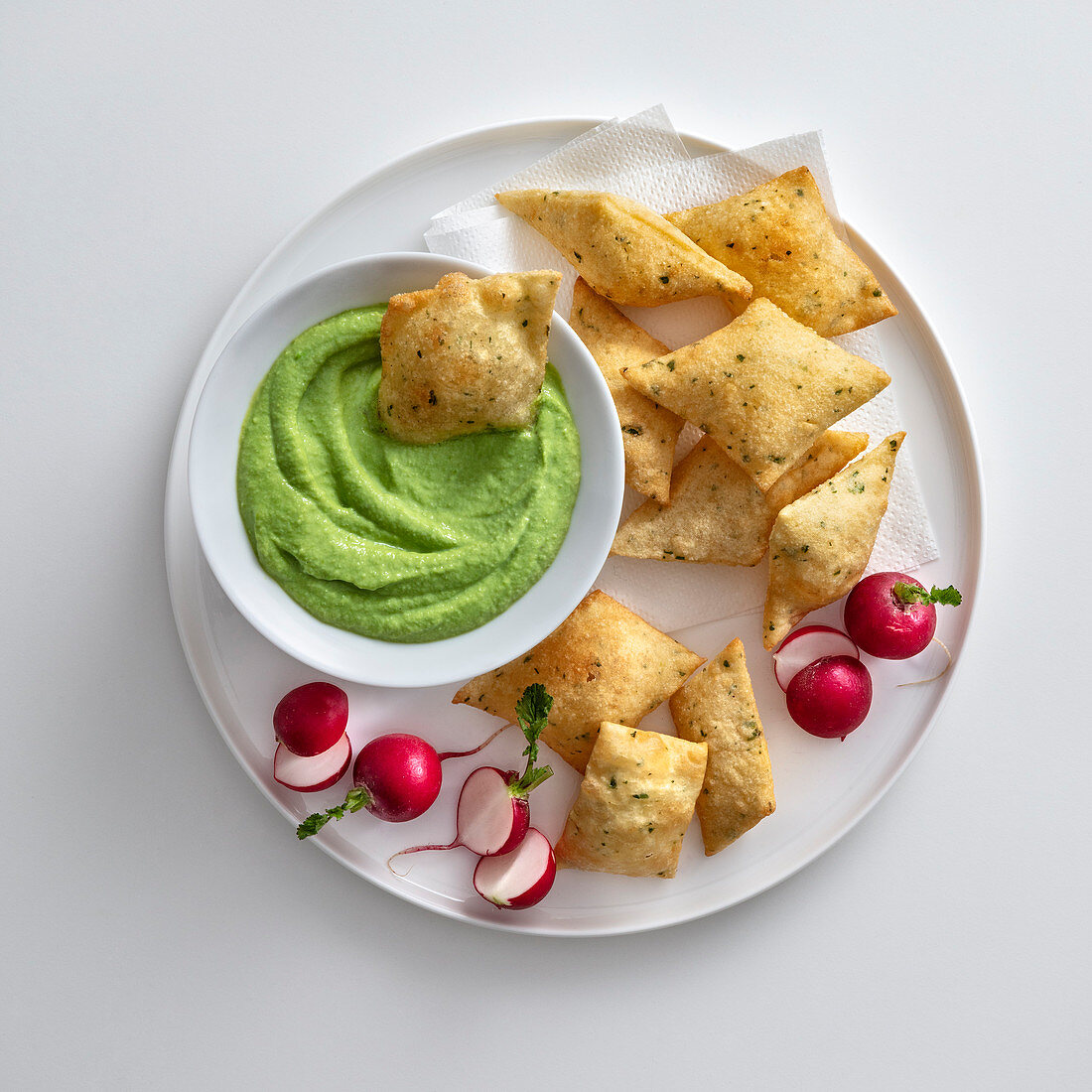 Fava bean cream with fried herb pillows and radishes