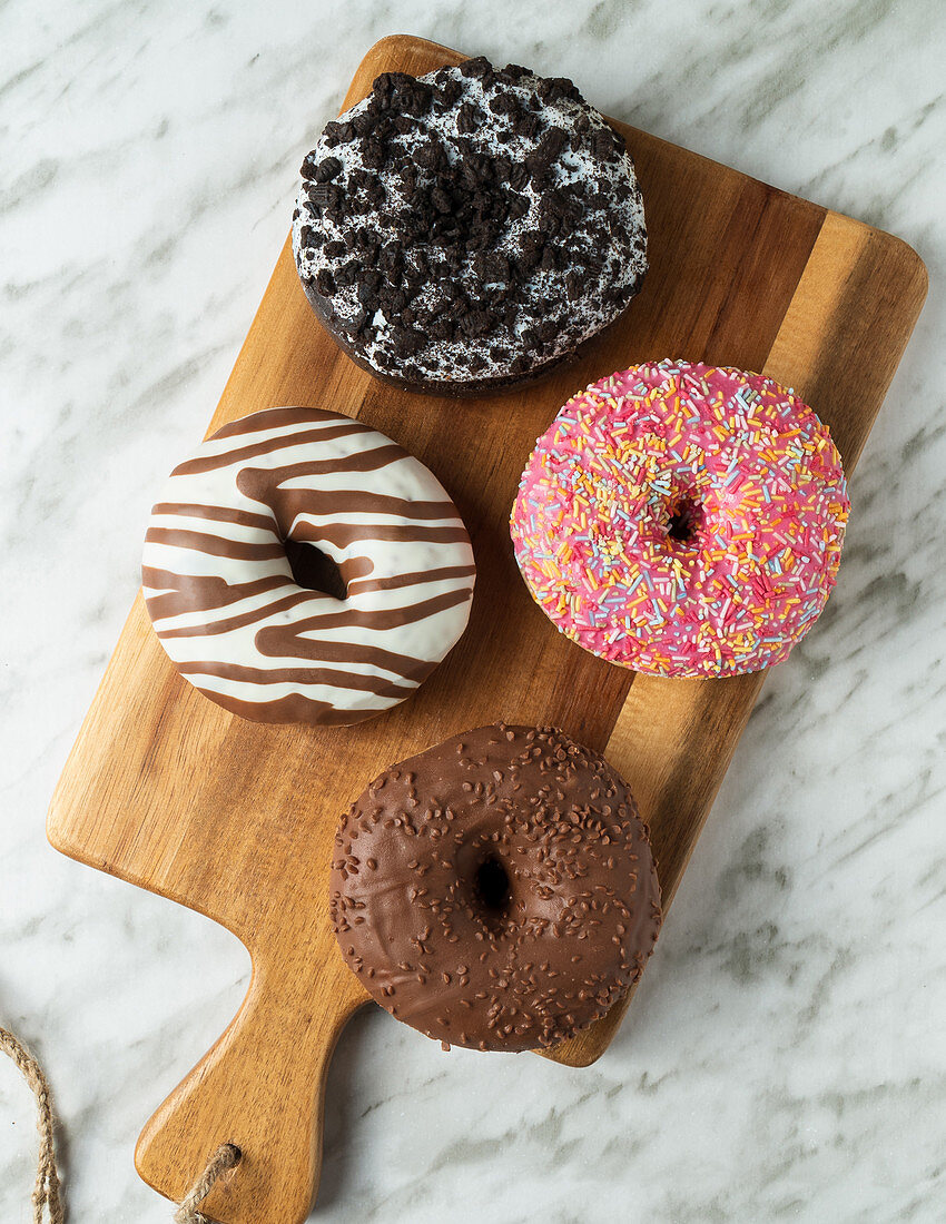 Four donuts on a wooden board