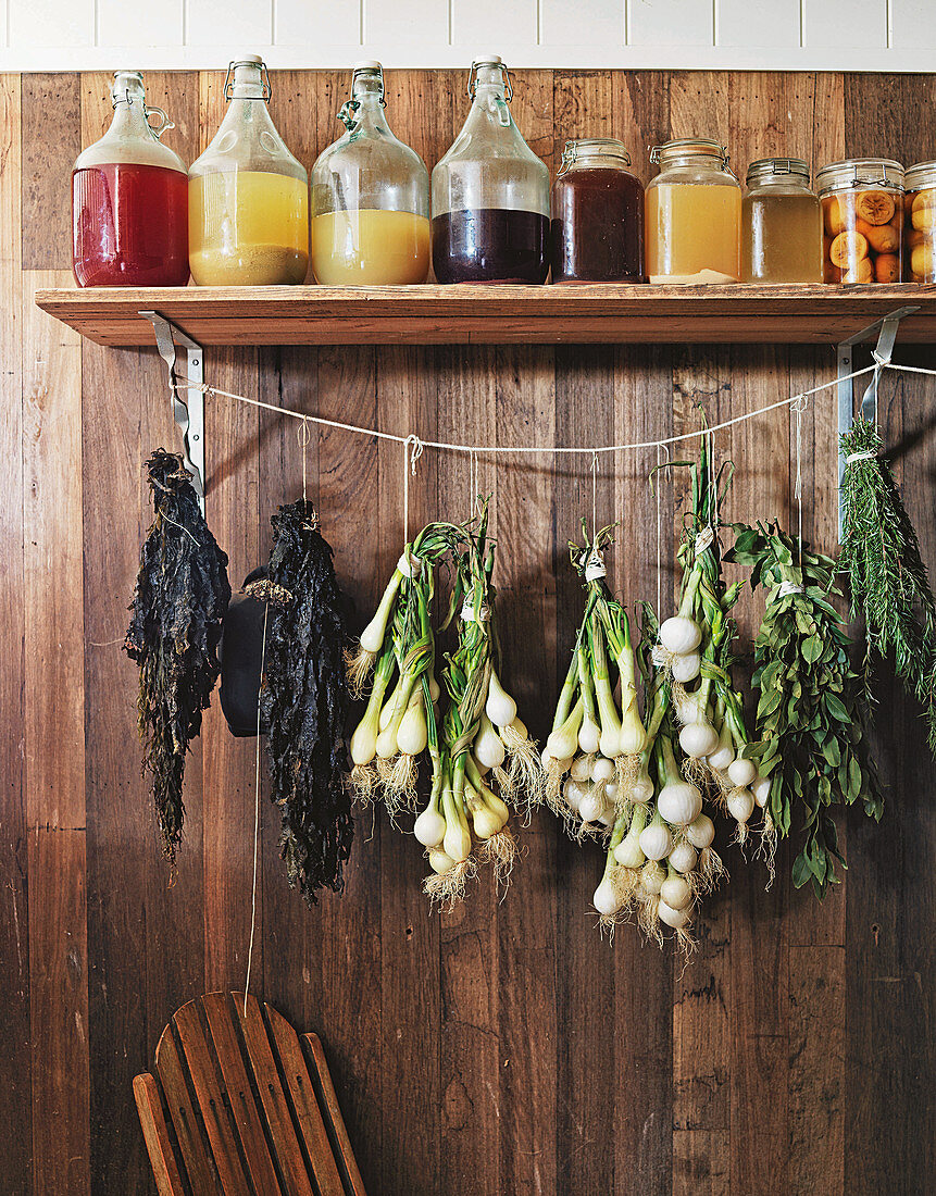 Wooden board with storage jars and herbs and onions hanging underneath