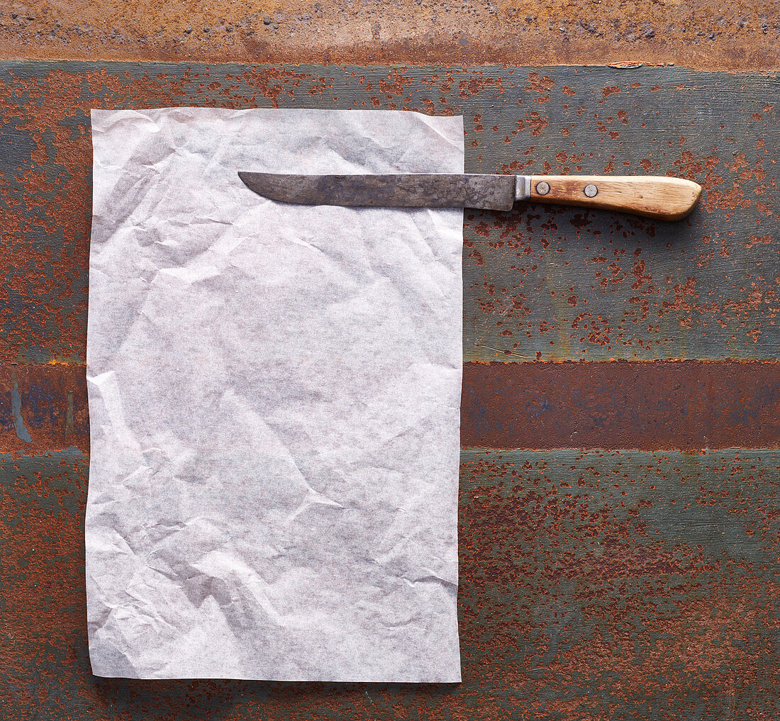Baking paper and a rusty knife on a metal surface