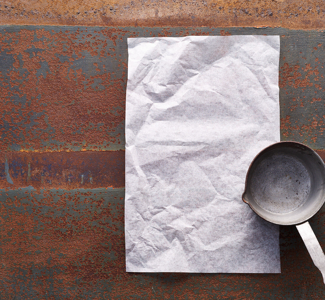 A saucepan and baking parchment on a rusty surface
