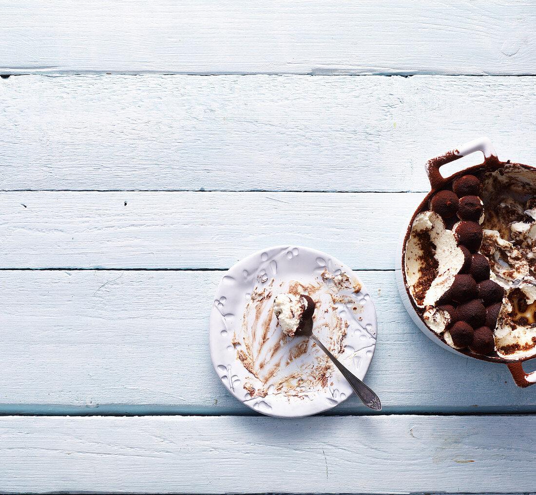 Empty dessert plate and tiramisu in a saucepan