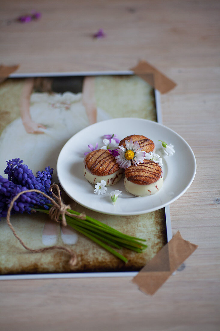 A plate of pastries next to hyacinth bunches