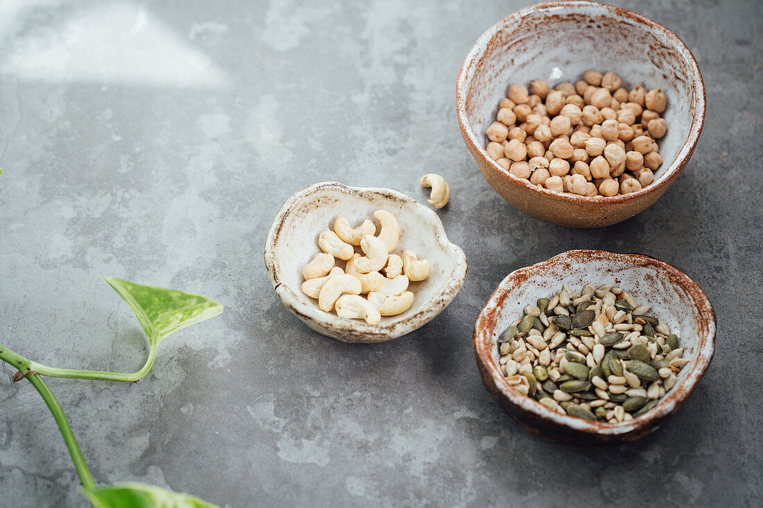 Seed mix, chickpeas and cashews in hand made clay bowls