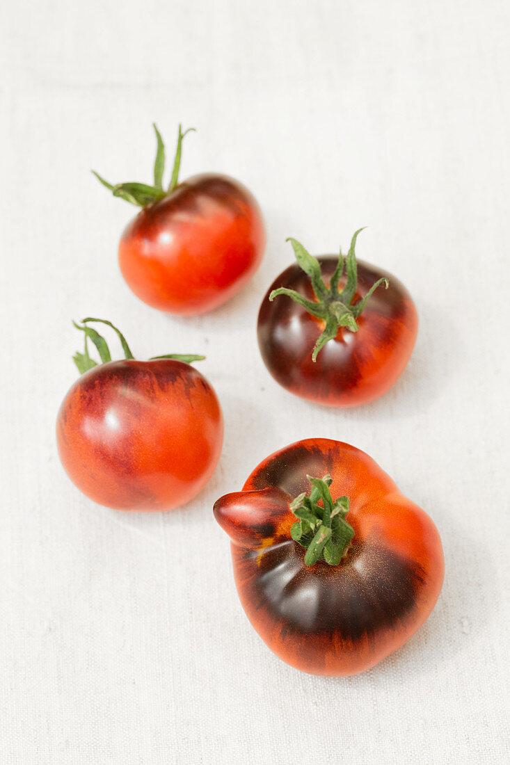 Four Indigo Apple tomatoes on a white background
