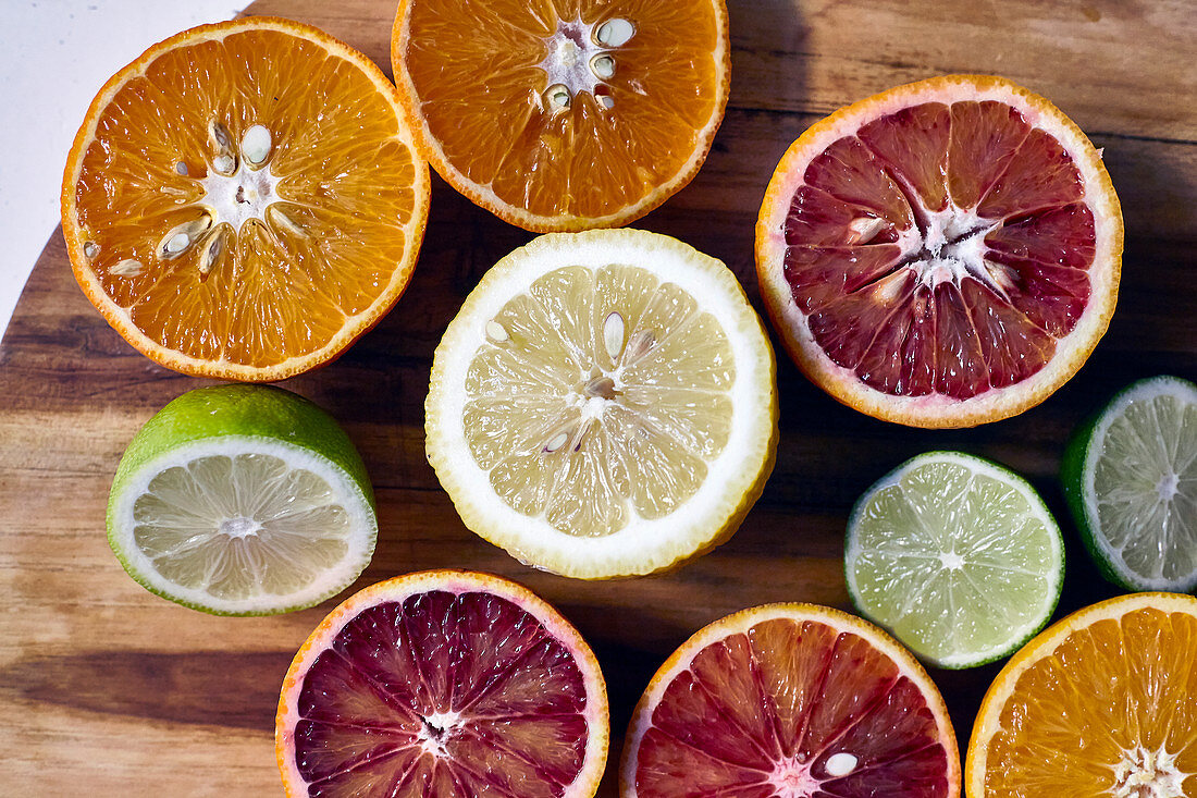 Various halved citrus fruits on a wooden cutting board