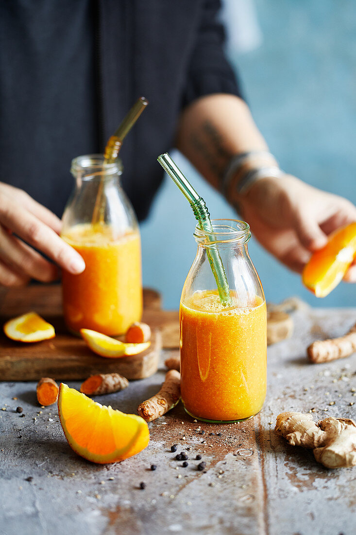 Orange and turmeric ginger drink in bottles