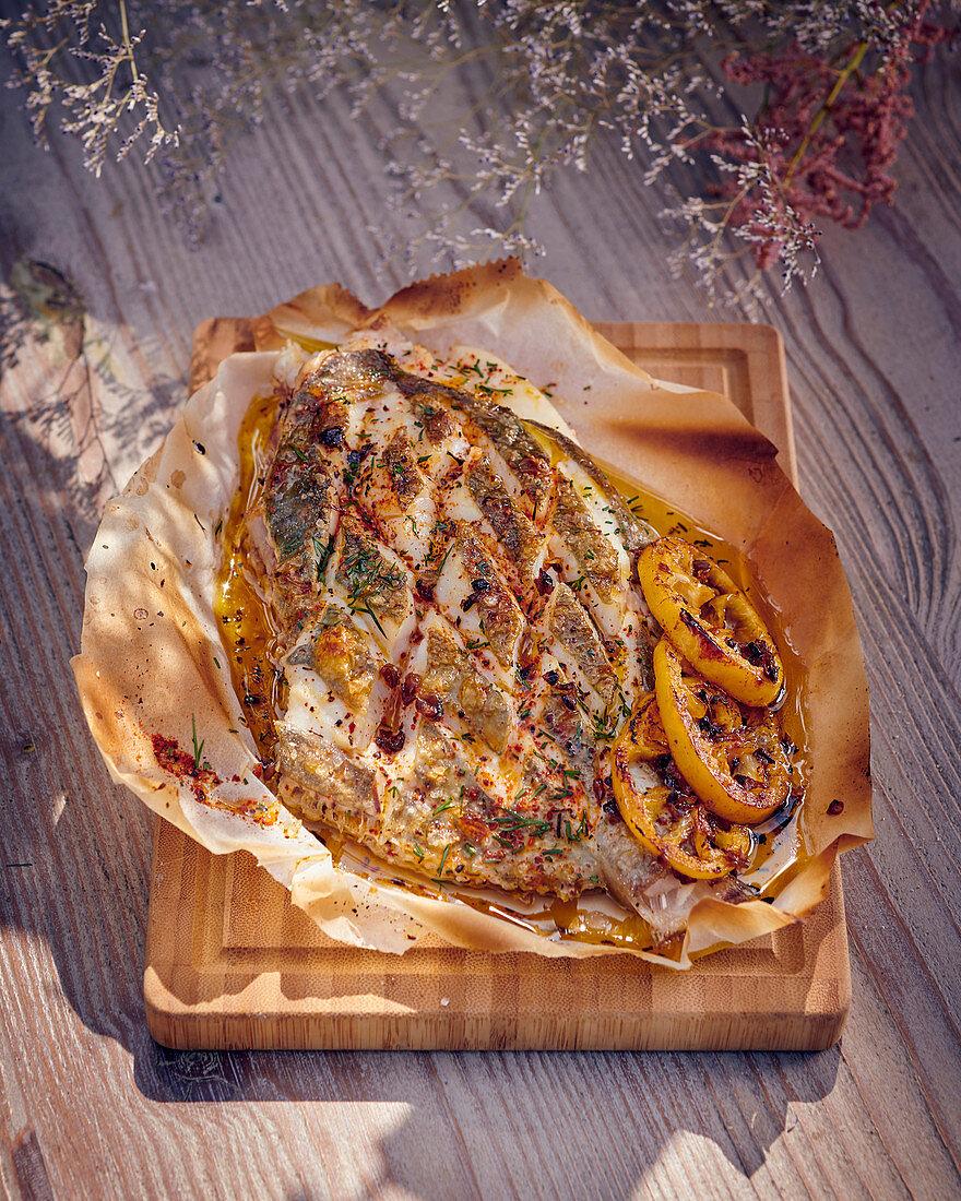 Flatfish with lemons on baking paper
