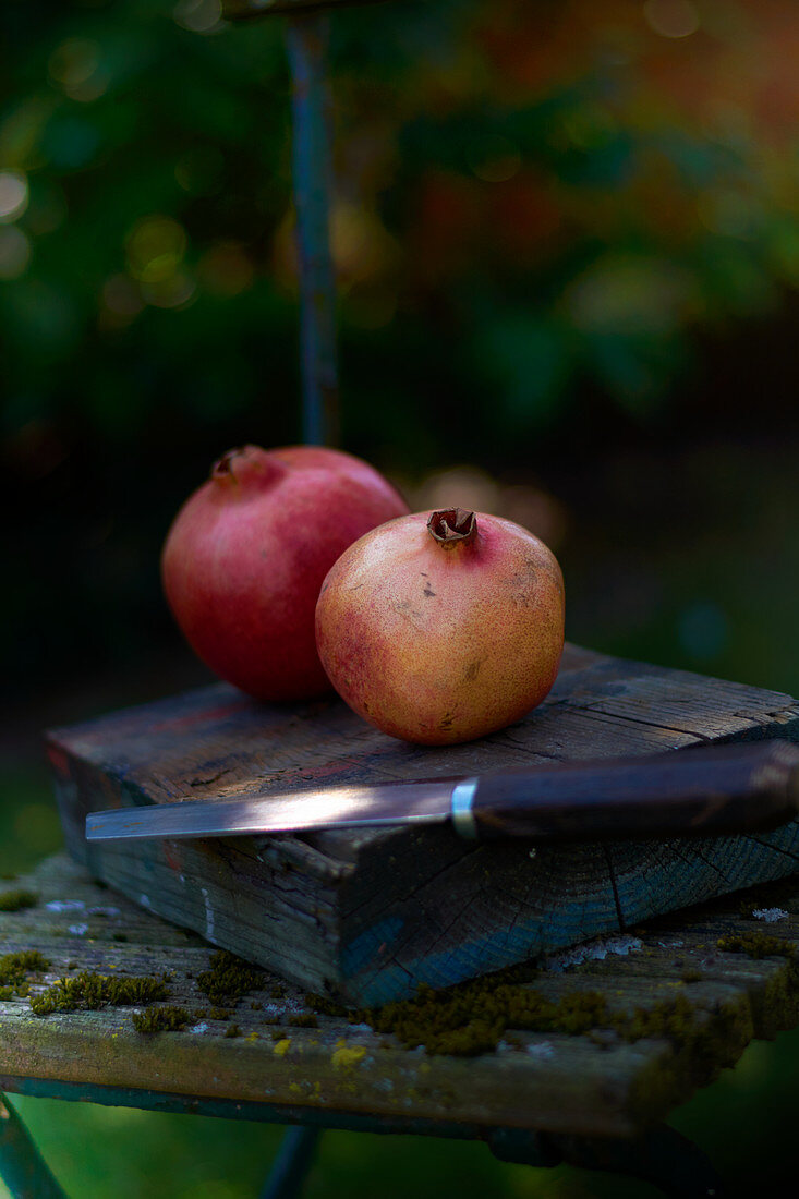 Two pomegranates with a knife on a wooden block