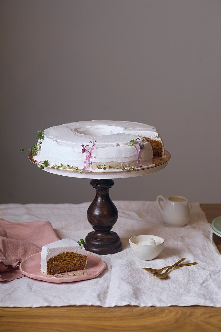 Vegan carrot cake with coconut cream frosting on wooden cake stand with one wedge cut and served on a plate