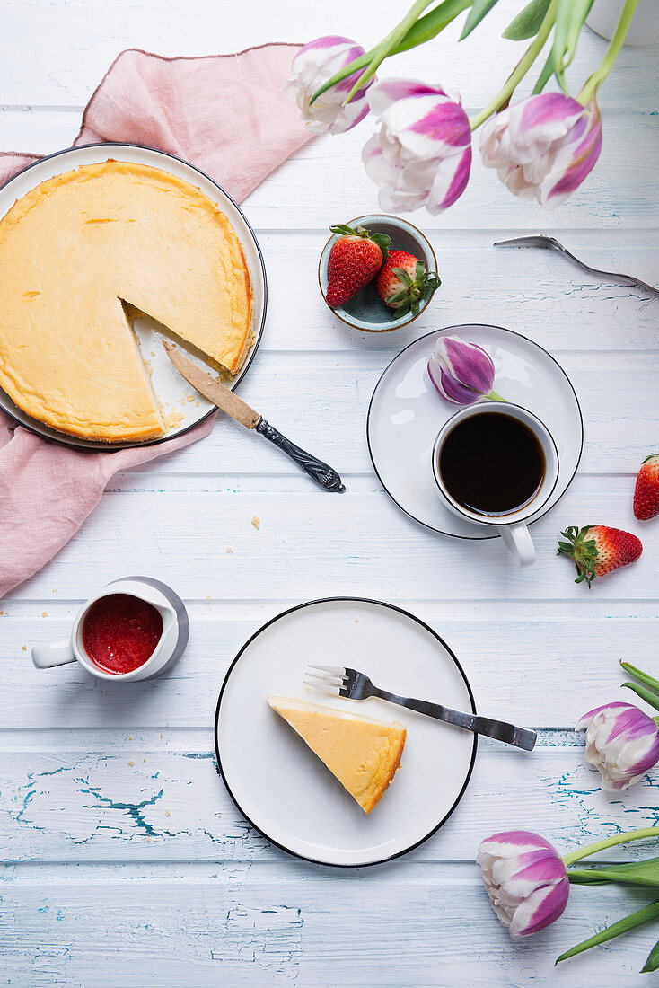Coffee served with vegan cheesecake, fresh fruits, strawberry sauce, and tulips