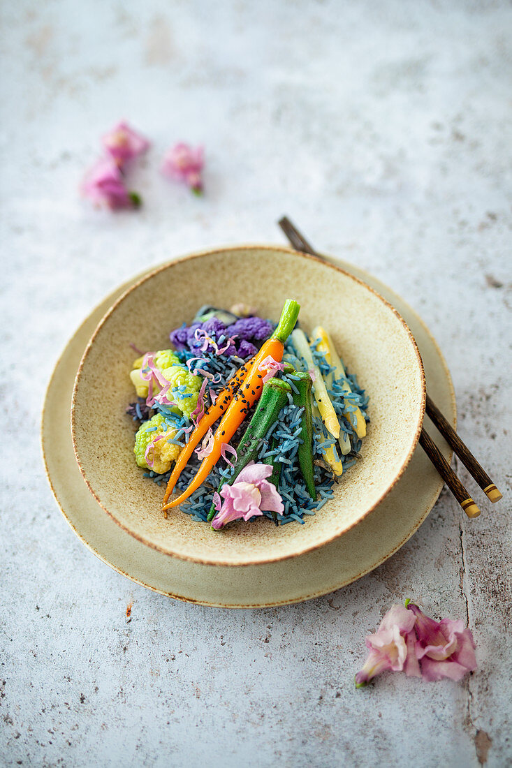 Blue rice with vegetables and edible flowers (vegan)