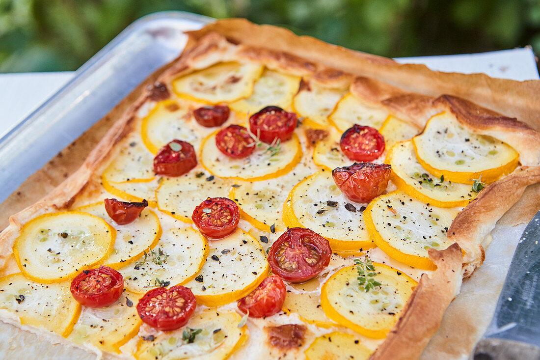 Tomato zucchini tart on a baking sheet