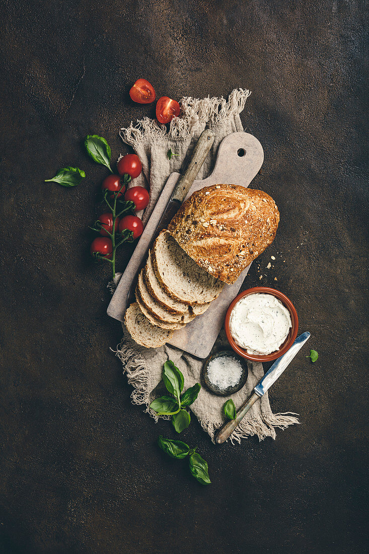 Ingredients for healthy home made sandwiches: Wholegrain bread, cream cheese, tomatoes and basil on rustic background