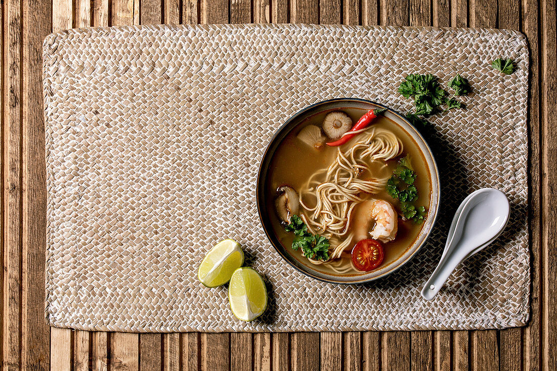 Asian spicy noodles soup with shiitake mushrooms and prawns, ingredients above on straw wicker napkin over wooden plank background