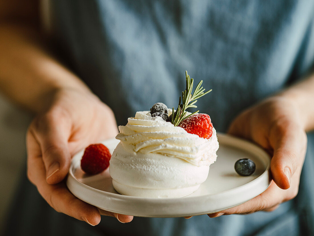 Woman hold plate with mini Pavlova cake decorated fresh berries and rosemary