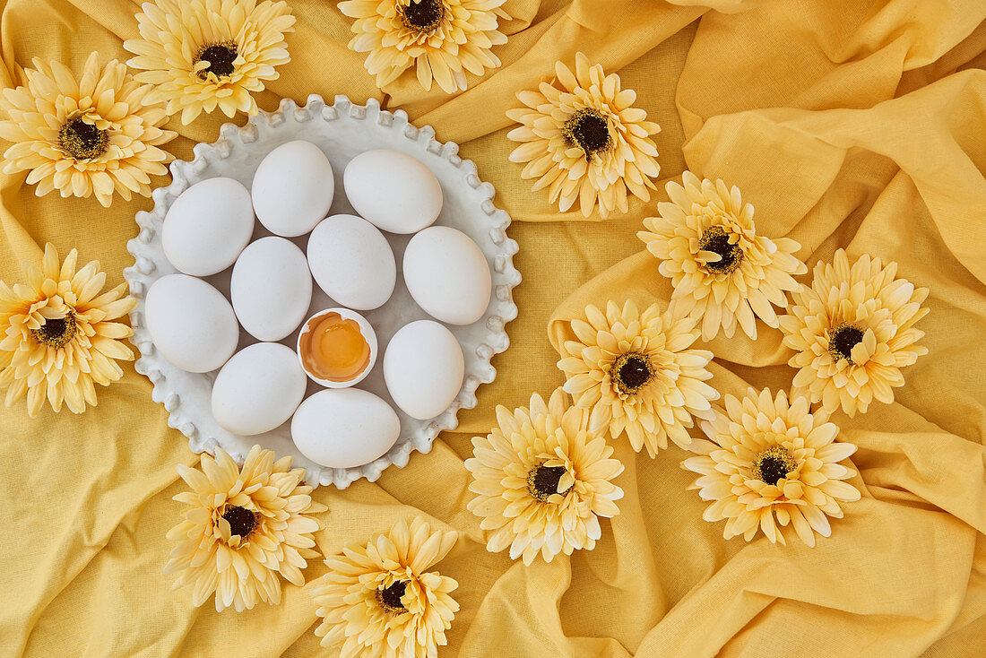 White eggs and yellow gerbera flowers