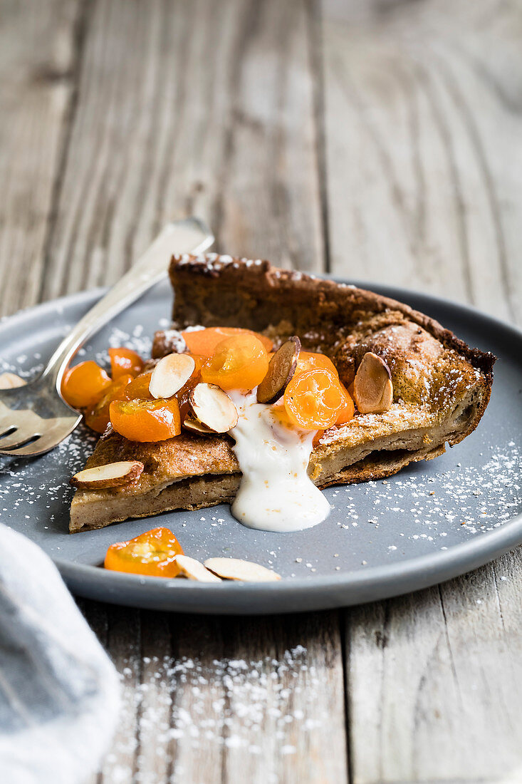 Cinnamon spiced almond dutch baby with honeyed kumquats, and a dollop of vanilla bean crème fraîche