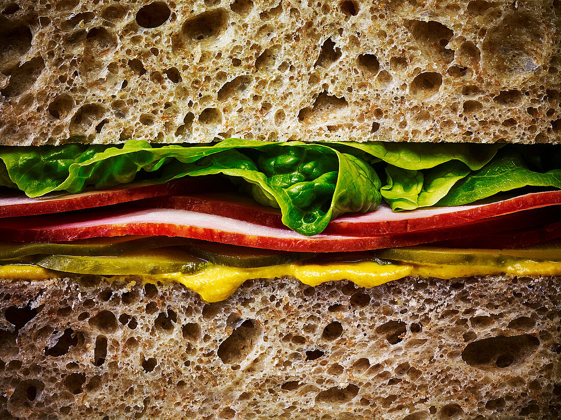 A ham salad sandwich with mustard on brown bread