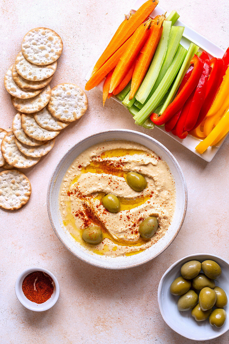 Red lentil hummus with sliced vegetables and crackers on the table