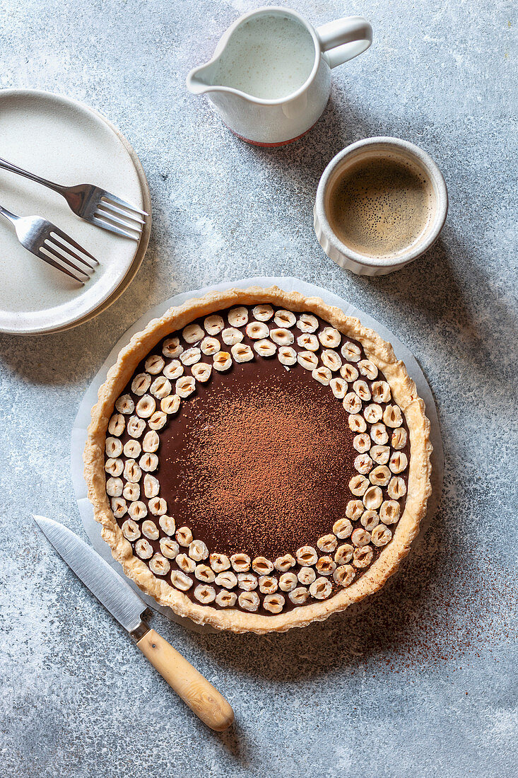 Chocolate hazelnut tart on the table with a cup of coffee and cream