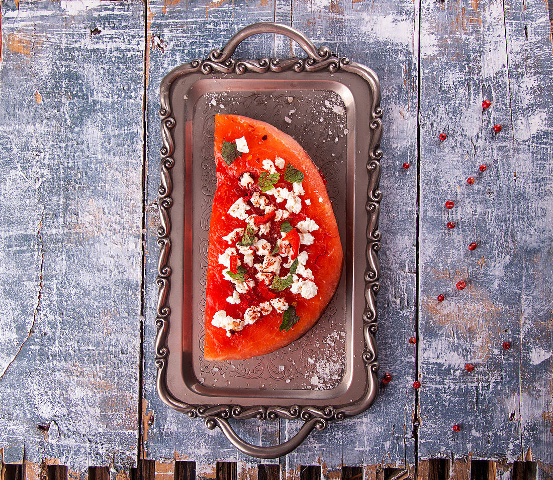 Grilled watermelon with feta cheese, chili pepper and mint on vintage tray