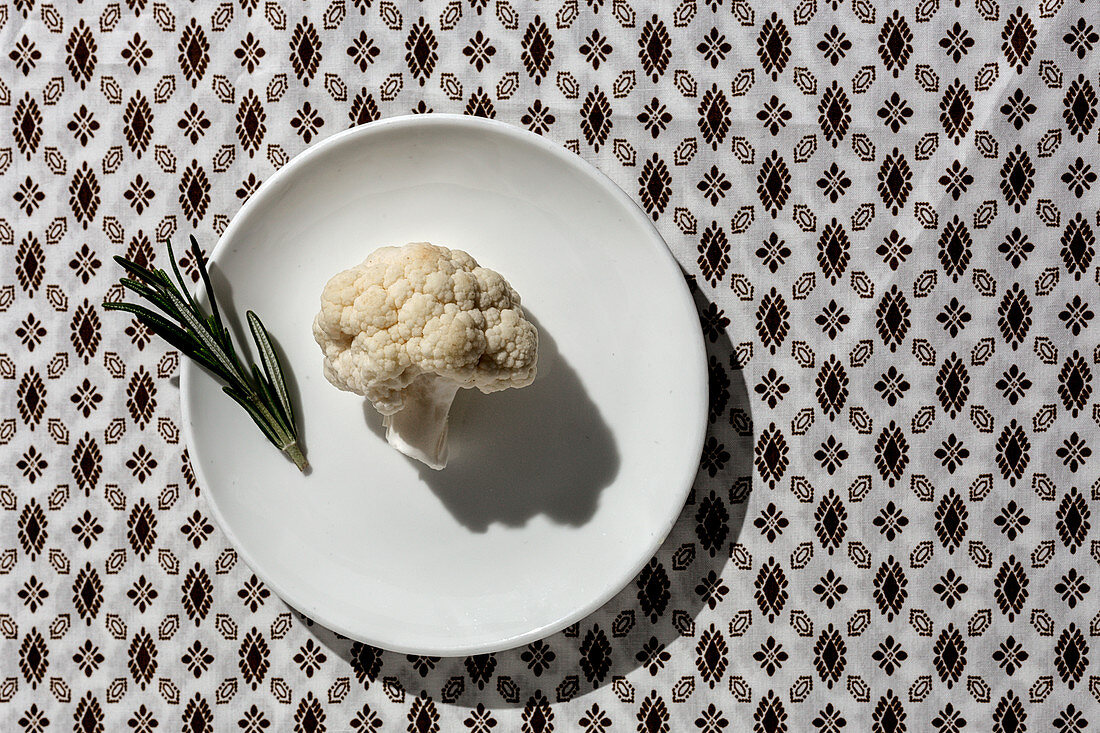 Raw cauliflower bouquet with rosemary from above with sunlight