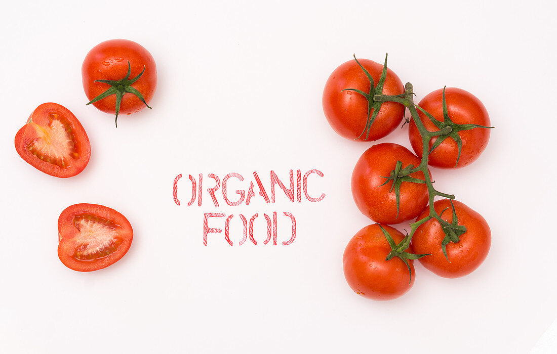 Clean ripe tomato placed near organic food writing on while background