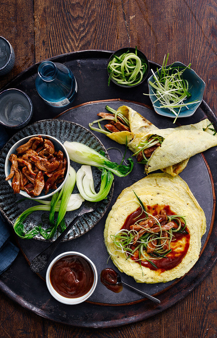 Asian wraps with duck meat, vegetables and spicy sauce