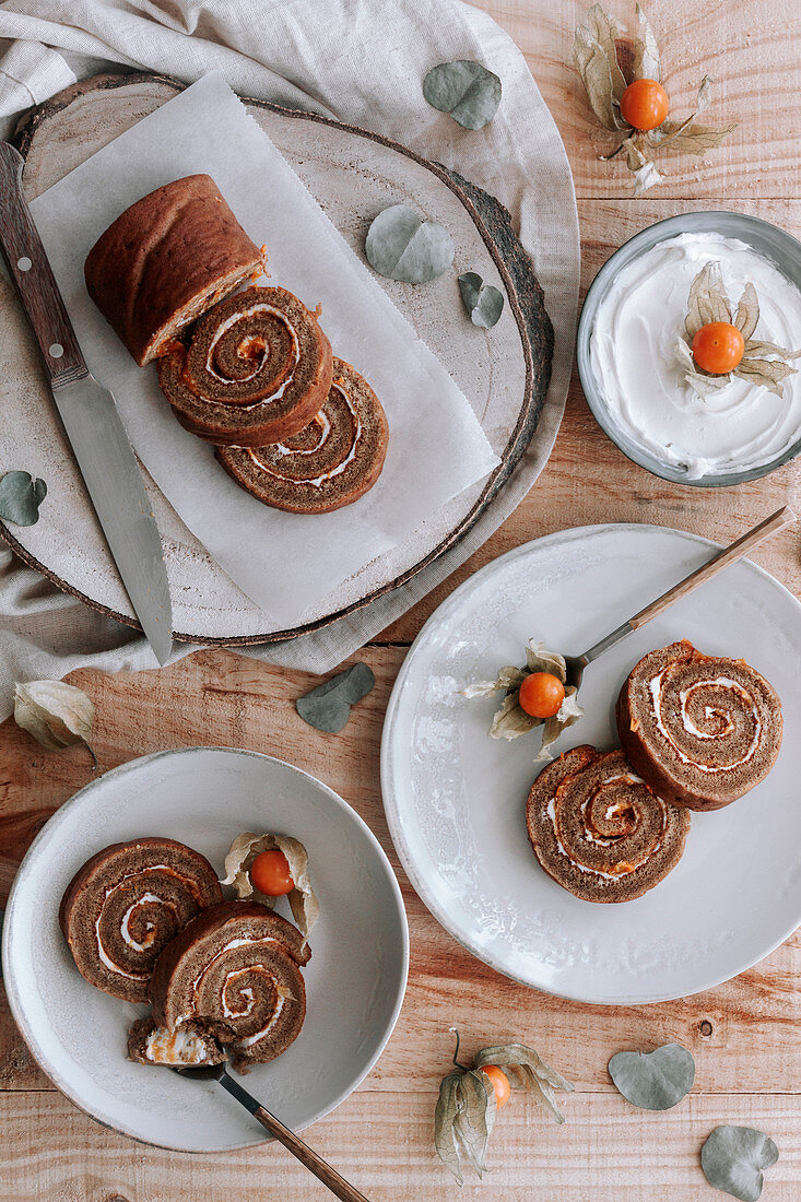 Homemade sweet roll cake with whipped cream and Physalis dried flowers