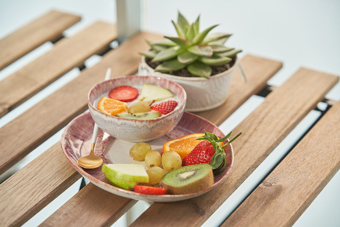 Healthy breakfast with yogurt and assorted colorful fresh fruits served on wooden table