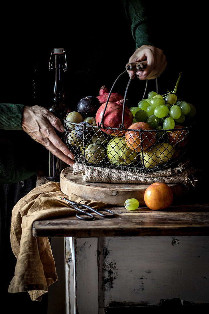 Crop senior person taking fruit from basket