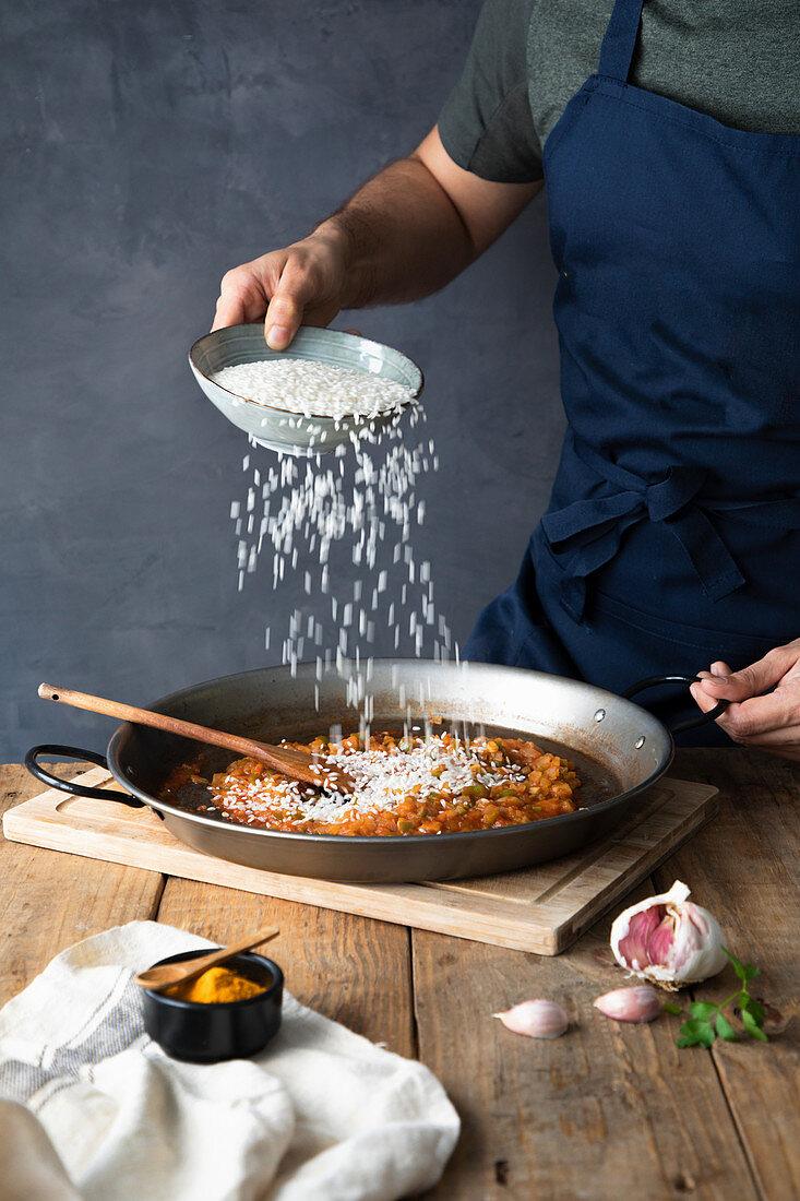 Adding white rice to chopped roasted ingredients on big metal pan