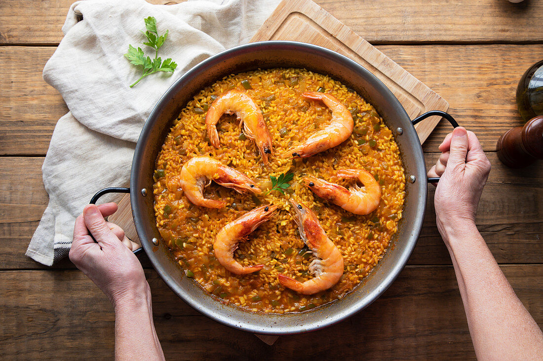 Paella with roasted shrimps against rustic table