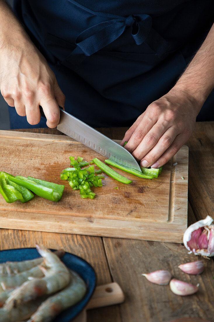Cutting green chili pepper on wooden cutting board, garlic and fresh raw shrimps