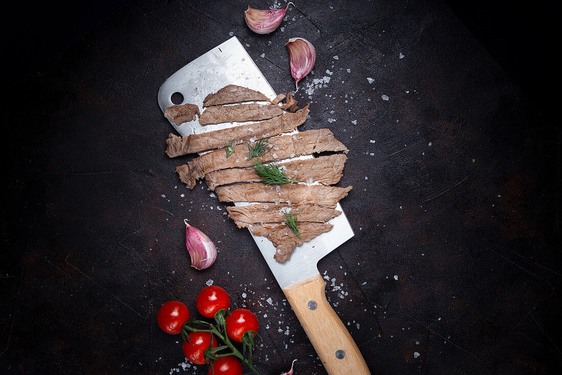 Huge knife with slices of fried meat placed near garlic cloves and tomatoes on black background