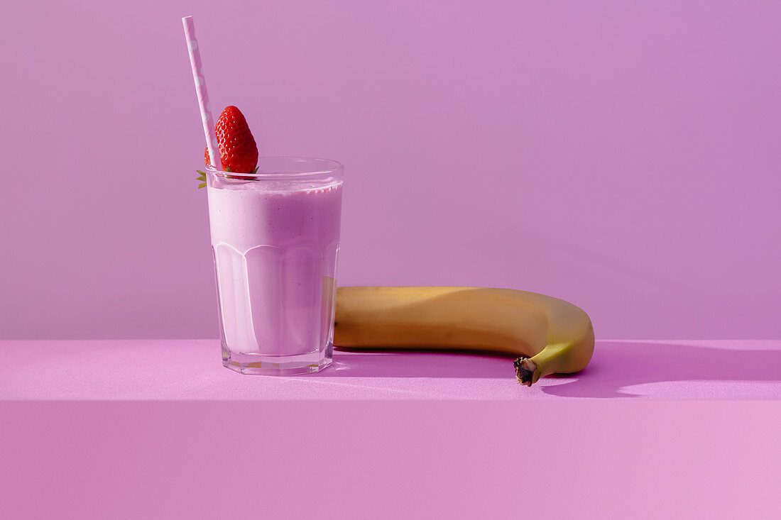Glass of delicious healthy dairy drink with fresh sweet strawberry and ripe banana on table in vivid purple light