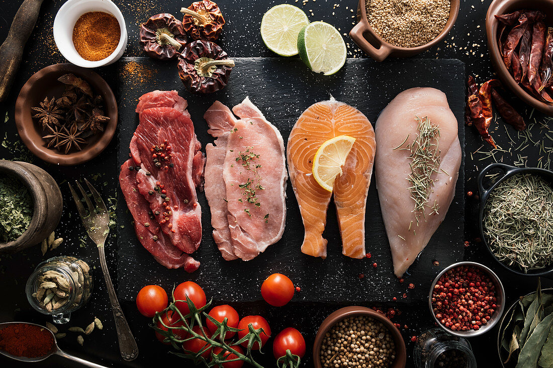 Fillet of beef, pork, chicken and fish on black wooden cutting board with different aromatic spices and seasonings
