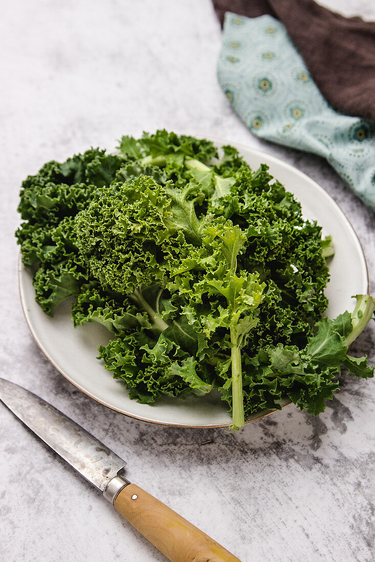 Plate with green leaves of ripe kale placed near knife