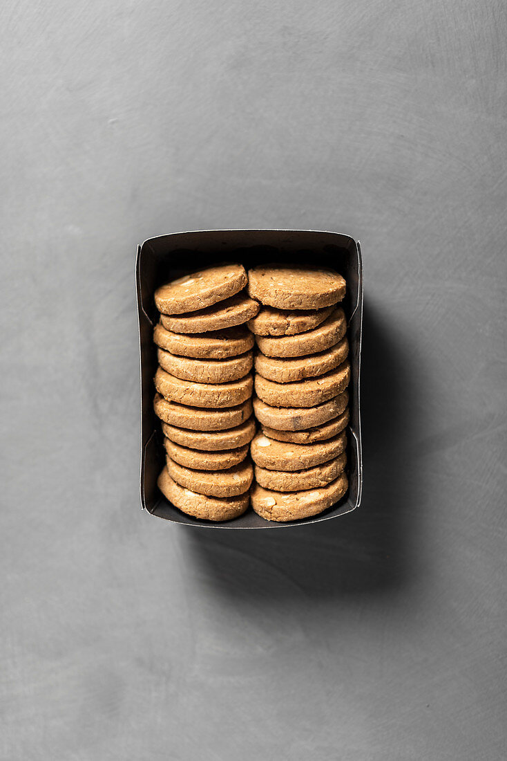 Spelt cookies with almonds in a box on a gray background