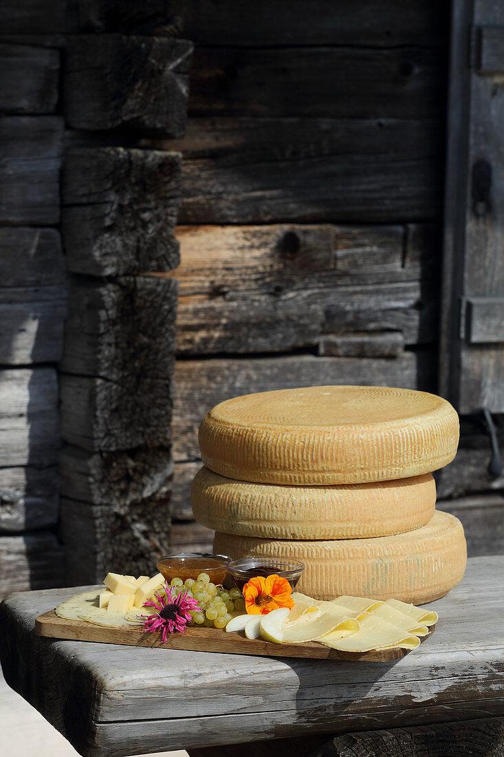 Brotzeitbrett und Käseräder auf Holztisch vor Almhütte