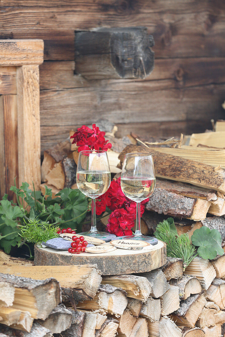 Two glasses of wine arranged with name tags on wooden discs outside Alpine cabin