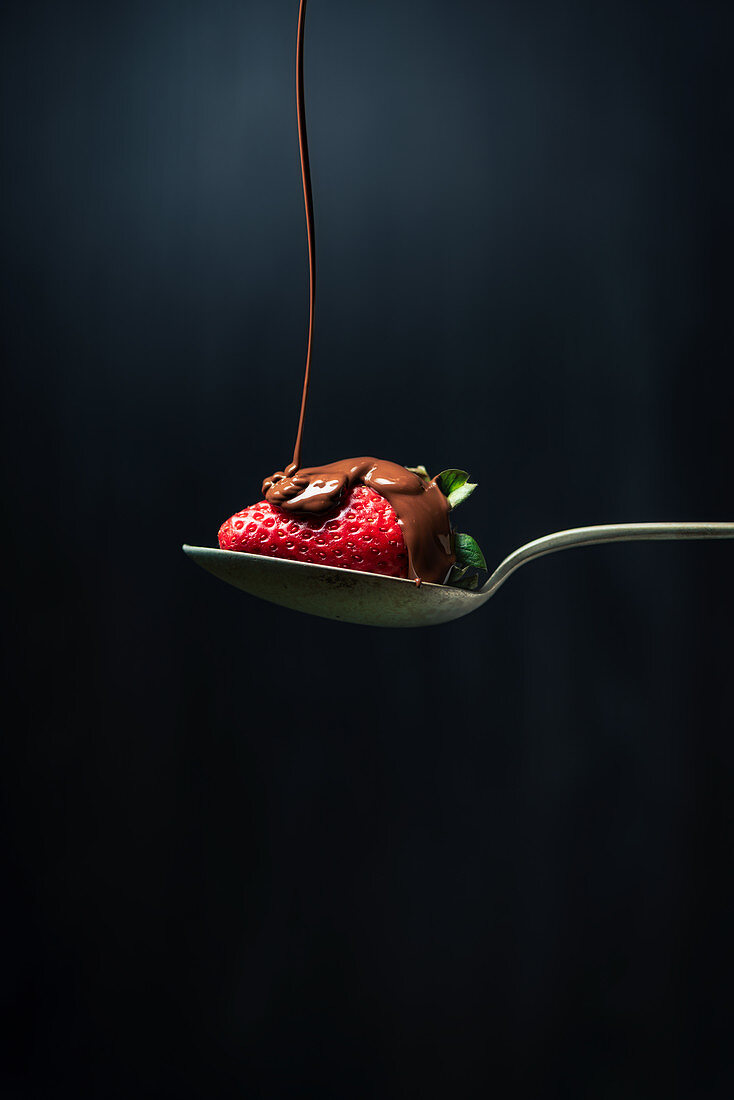 Chocolate being drizzled onto a strawberry on a spoon